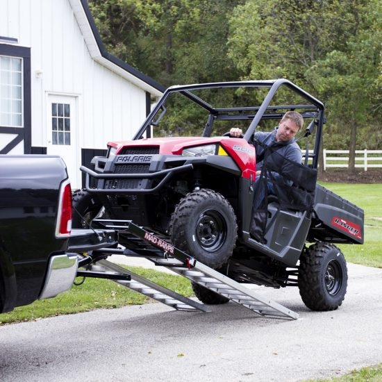 Farmer loading ATV with MAD-RAMPS onto pickup truck